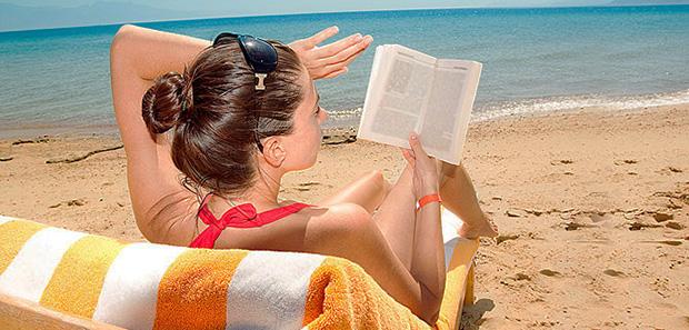 Дама на пляже с книгой